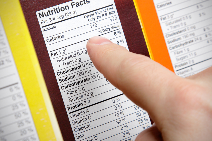 A concerned shopper checks the nutrition labels of various boxes of cereal.