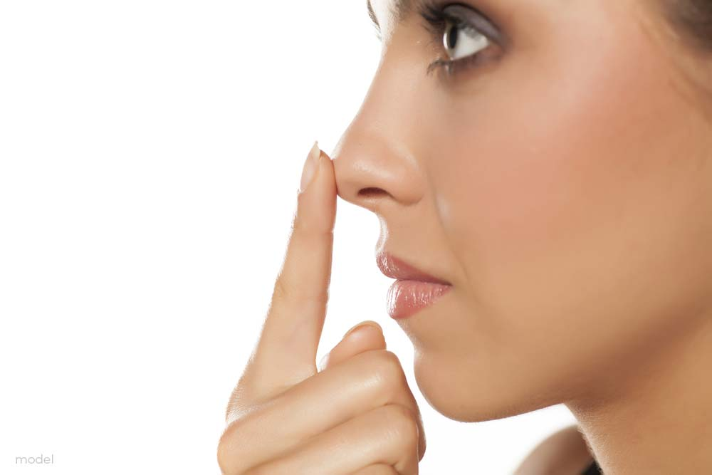 Woman touching the tip of her nose
