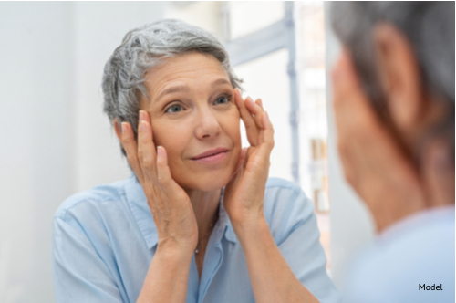Portrait of mature woman massaging her face while checking wrinkled eyes in the mirror thinking about getting a mini facelift-img-blog
