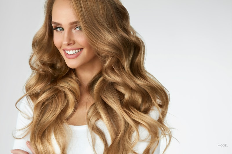 Young woman with long, thick, healthy, wavy hair.