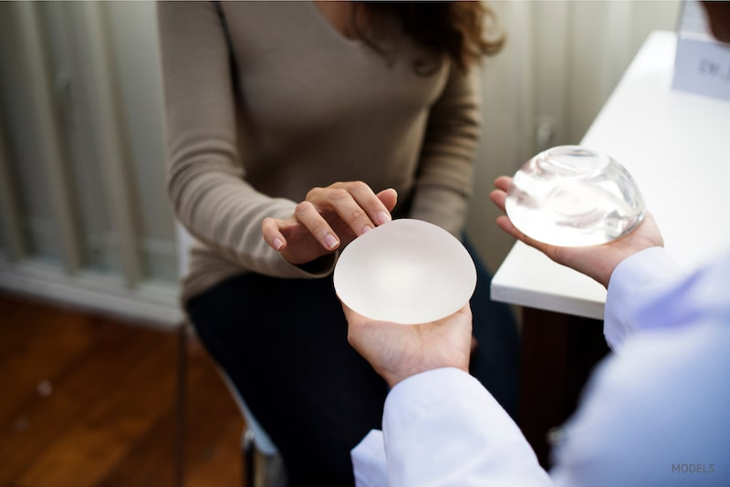 woman choosing between textured and smooth breast implants