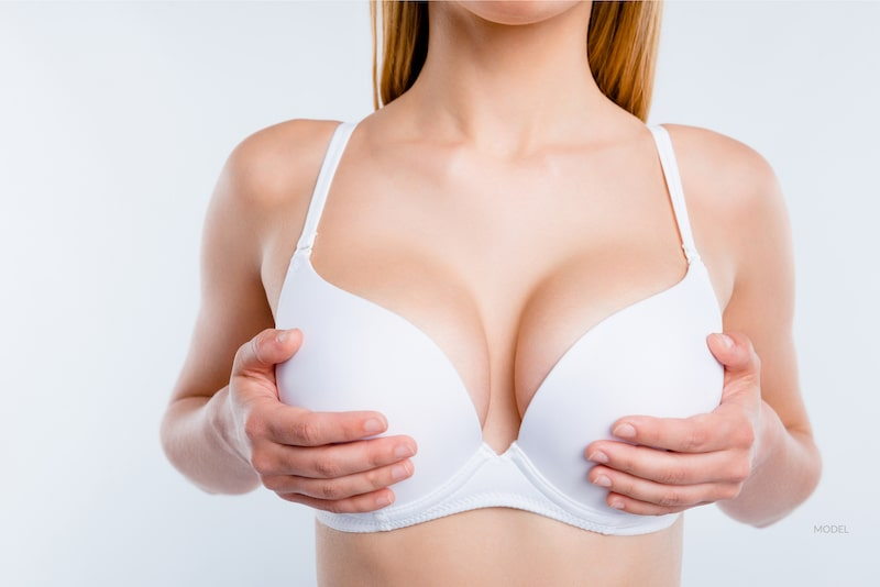 Woman holding up her larger breasts over white bra.